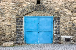 stone wall with arch and blue metall door