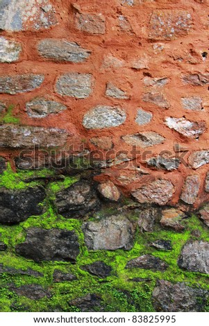Stone wall with moss growing from bottom