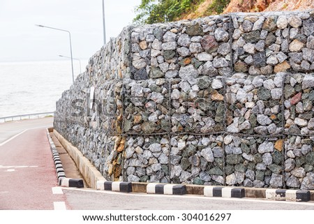 Stone wall with wire mesh for falling rock protection from mountain