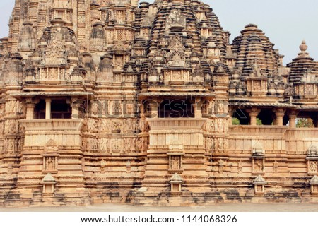 Stone walls of designed in 10th century Hindu temple in ancient Indian city Khajuraho. UNESCO World Heritage Site