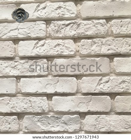 Stone white wall with a dark bronze rose in the upper left corner #1297671943