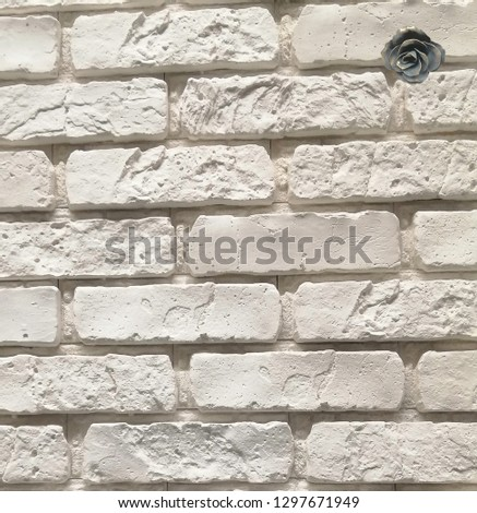 Stone white wall with a dark bronze rose in the upper right corner #1297671949