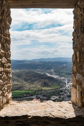 Stone window of a medieval castle from which you can see the horizon composed of a sky with white clouds and dark green mountains, the access road and some nearby construction.