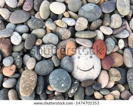 Stone with a painted smile. On the shore, one stone stands out from the others. On a small stone is an image of a happy face. Concept: joy, happiness, positive, kindness.