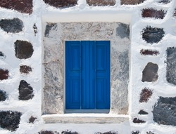 Stoned wall with blue window from a house in Santorini Island