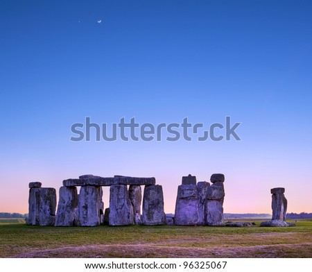 Stonehenge at twilight, the historic site on green grass under blue sky. Stonehenge is a UNESCO world heritage site in England with origins estimated at 3,000BC.