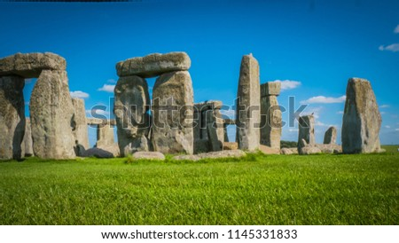 Stonehenge complex at unesco world heritage site near Salisbury in England. Summer holidays destination in the UK, Europe. Green countryside landscape with blue sky on a summer day in Great Britain.