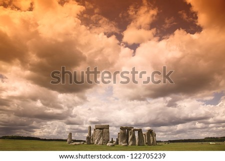 Stonehenge historic site on green grass under blue sky. Stonehenge is a UNESCO world heritage site in England with origins estimated at 3,000BC