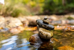 Stones arranged in zen towers by the river bed on a summers day