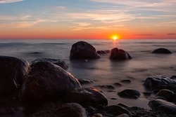 stones at sea at sunset and in the long exposition
