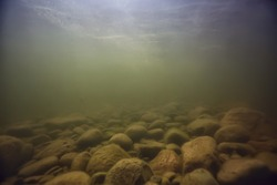 stones at the bottom underwater landscape, abstract blurred under water background