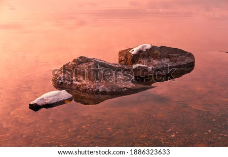 Stones covered by snow  on calm water background in early winter season on sunset time. Photo stock ©