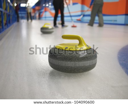 Stones for game in curling on ice. Playing people on the background. The concept - the productive leisure, a healthy way of life.