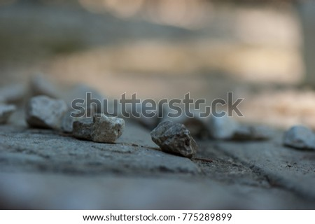 stones in the foreground and blur in the background, stones are light grey and the background grey and  orange colors, stones are in a group, the focus is on two stones and the others are blur  #775289899
