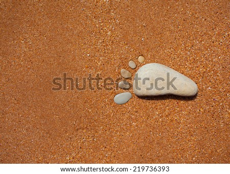 stones in the shape of feet representing footprint in the sand #219736393