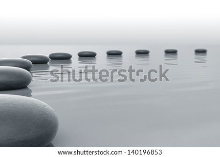 Stones in water forming a circle towards the horizon