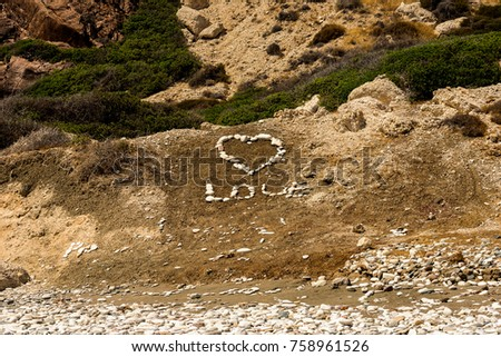 """Stones inscribed """"Love"""" word with a large heart on a beach at a popular Aphrodite Rock in Cyprus #758961526"""