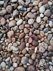 stones lies on the ground, multicolored river pebbles stones randomly lie on the ground.