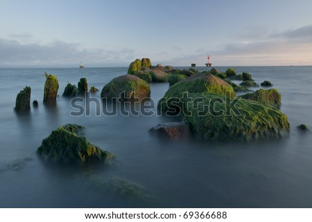 stones of the old pier on the beach with a lighthouse in the background
