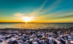 Stones on a beach with sunset on the ocean sea. Landscape photo of sunrise or sunset on a natural beach in Piran, Slovenia.