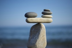 Stones pile background. Scales balance. Balanced stones on the top of boulder. To weight pros and cons. Balance of stones on a blue sky background with a copy space.