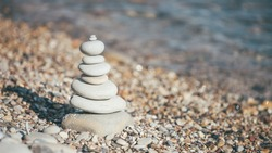 Stones piramide on pebble beach - harmony, meditation, patience and peace of mind concept