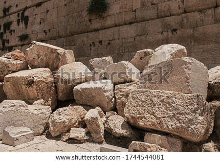 Photo of  stones thrown by the romans from the second temple to the street below after the destruction of the temple in 70 CE with the Western Wall in the background