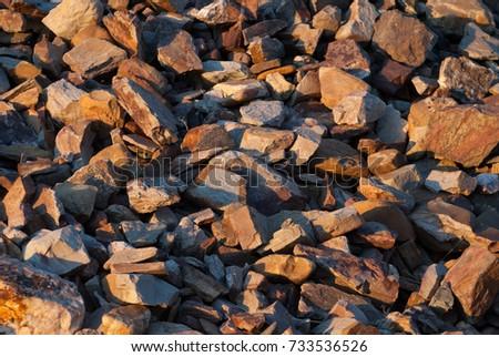 Stones thrown on the ground, sandstone and slate, reddish tones.