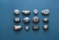 Stones with painted Zodiac signs on color background