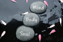 Stones with words Mind, Body, Soul and flower petals in water, flat lay. Zen lifestyle