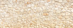 Stonewall background texture. Cobblestone empty with row of beige strong stones