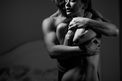 Stong handsome man with muscled body embracing beautiful woman. Love concept.