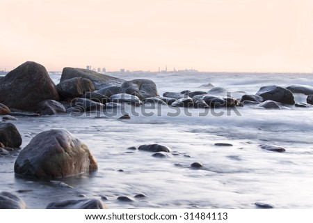 Stony shore with view of Tallinn. Smooth water. Winter shot.