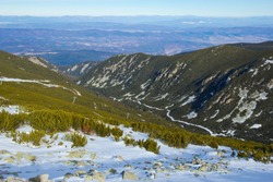Stony slope of Vitosha Mountain, view of the Bulgarian city of Sofia. Winter bright sunny day. the slopes are covered with snow, with a small amount of vegetation - blueberry bushes.