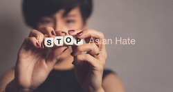 Stop asian hate hashtag, support Asian americans communities, stop hate crimes campaign. A beautiful Asian woman hold letter word