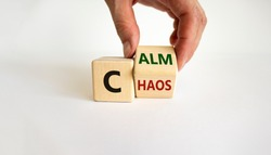 Stop chaos, time to calm. Male hand turns a wooden cube and changes the word 'chaos' to 'calm'. Beautiful white background, copy space. Business and chaos or calm concept.