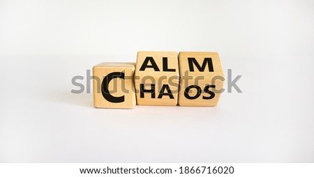 Photo of  Stop chaos, time to calm. The words 'chaos' and 'calm' on wooden cubes. Beautiful white background, copy space. Business and chaos or calm concept.