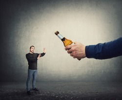 Stop consuming alcohol concept. Man refuse to take a bottle of beer from an giant hand, as metaphor for win against addiction. Guy reject drinking alcohol. Facing bad habits, healthy lifestyle