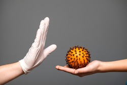 Stop coronavirus, prevention, two hands and a symbolic virus.