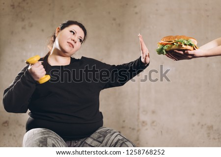 stop eating fast food, go in for sport.plump girl refuces jink food. healthy life, health and body care.closeup photo