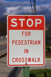 Stop for pedestrian in crosswalk sign at a corner.