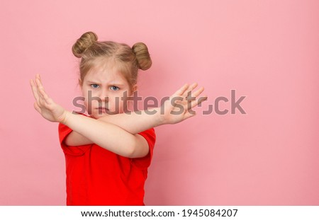 Stop gesture. Little girl with arms crossed on pink background with copy space. Child protest, rejection. Stock foto ©