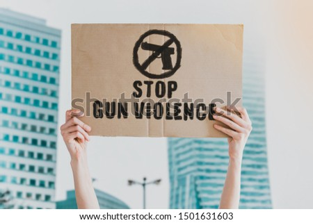 Stop gun violence phrase drawn on a carton banner in men's hand. Human holds a cardboard with an inscription: Stop gun violence phrase