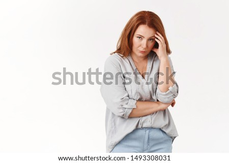 Stop it. Irritated displeased annoyed redhead middle-aged pressured woman touch temple look from under forehead scorn bothered cannot stand anymore displeased intense white background