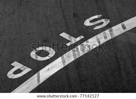 Stop label and line on the asphalt road with braking tracks across it
