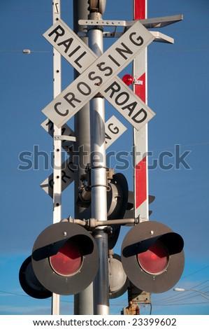 Stop lights at rail crossing under bright blue sky