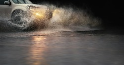 Stop motion, high resolution image of   splash by a car through flood water after hard rain.
