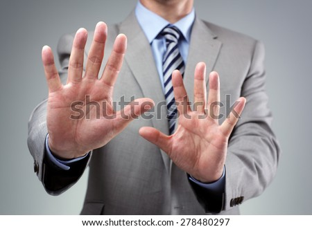 Stop or fear gesture from businessman in suit holding hands up