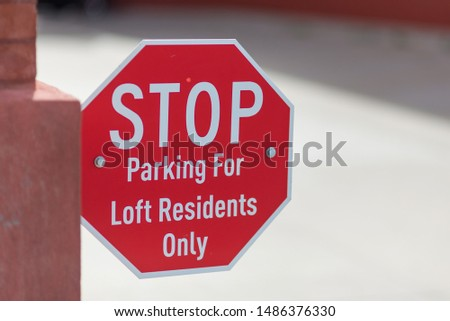 STOP - Parking for Loft Residents Only sign, close up with concrete in the background.