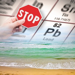 Stop pollution from dangerous lead and heavy metals in seawater - concept with hand holding a stop sign against a lead chemical element with the Mendeleev periodic table on seawater background.